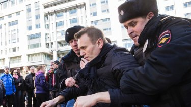 Alexei Navalny is detained by police in downtown Moscow on Sunday.