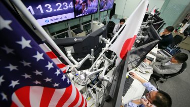 Money traders watch the day's exchange rate at a foreign exchange brokerage in Tokyo.