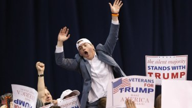 A supporter of Republican presidential candidate Donald Trump tries to pump up the crowd before the Chicago rally was cancelled on Friday.