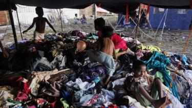 Ethnic Rohingya children play on a pile of clothes donated by local residents at a temporary shelter in Langsa, on Monday.