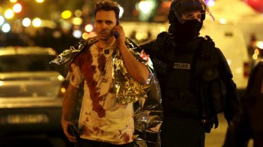 A French policeman assists a blood-covered victim near the La Bataclan concert hall.