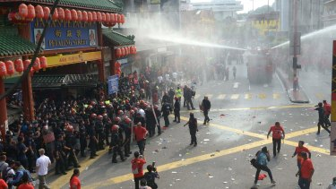 Riot police fire a water cannon at 'red-shirt' protesters in Kuala Lumpur's Chinatown neighbourhood.