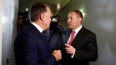 Environment and Energy Minister Josh Frydenberg has an argument with Labor MP Joel Fitzgibbon on energy issues as they cross paths at Parliament House.