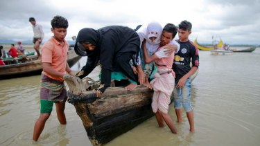 Bangladeshi villagers help two elderly Rohingya women get down from a boat after crossing a canal at Shah Porir Deep, in Teknak, Bangladesh