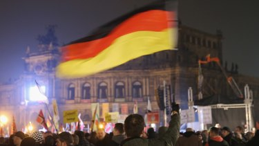 Supporters of the Pegida movement, including a man waving a German flag, gather on October 19, on the first anniversary of the first Pegida march.