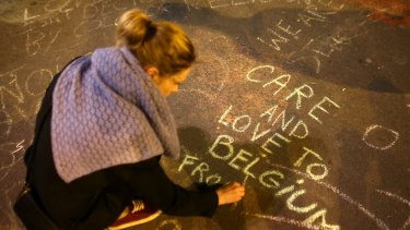 A woman writes a message on the ground as people leave tributes at the Place de la Bourse in Brussels.