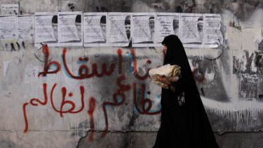 "A women carries bread past a wall in the village of Karzakan, Bahrain, with graffiti reading ""our demand is the fall of the unjust regime""."