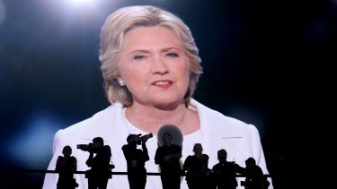 Photographers stand as Hillary Clinton, 2016 Democratic presidential nominee, is seen speaking on a screen during the Democratic National Convention (DNC) in Philadelphia. Her campaign was marred by the hack.