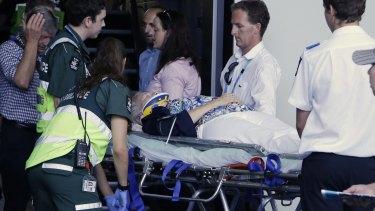 The injured woman is taken away by paramedics.