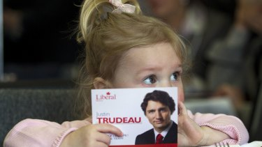 Two-year-old Ella-Grace, daughter of Liberal candidate Justin Trudeau, holds her father's election postcard in 2011.