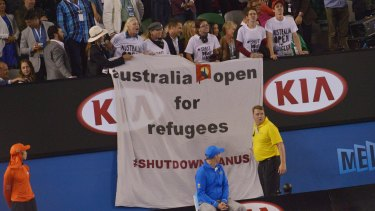 Protesters unfurl a banner during the men's final, drawing attention to the plight of refugees on Manus Island.