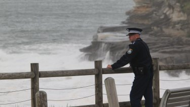 Police watch on as emergency services search for missing swimmer Endicott Ackerman, 20, south of Bondi Beach.