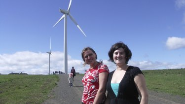 Jarra Hicks and Nicky Ison with the two wind turbines, Gale and Gusto, at Hepburn Wind.