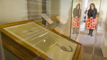 Director of the Parliamentary Art Collection Justine van Mourik with a Magna Carta that is on display at Parliament House.