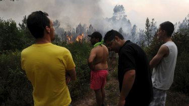 Residents watch on as Portuguese firefighters working to stop a forest fire from reaching the village of Figueiro dos Vinhos.