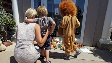 Sarah Madison (left) with her son Beckett, 3, and daughter Quinn, 5 (in costume) outside Dr Walter Palmer's River Bluff Dental clinic where a stuffed animal collection is growing in protest over Cecil's killing.