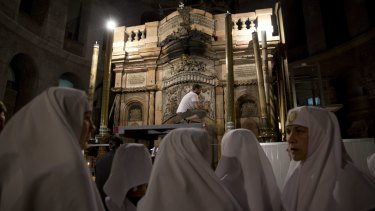Christian nuns watch as renovation begins at the Church of the Holy Sepulchre in Jerusalem's Old City.