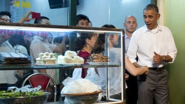 The US President greets women at the door as he walks from the Bun Cha Huong Lien restaurant.