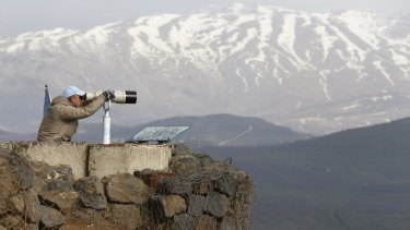 A member of the United Nations Disengagement Observer Force (UNDOF) looks through binoculars at Mount Bental, an observation post in the Israeli occupied Golan Heights. A UN peacekeeper was killed by cross-border shelling between Israel and Hezbollah.