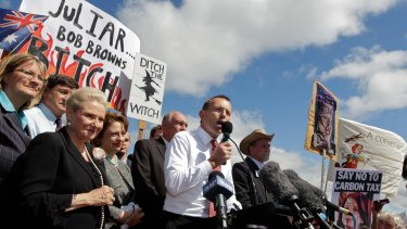 """Then opposition leader Tony Abbott in front of a """"ditch the witch"""" poster at a rally outside Parliament House in 2011."""