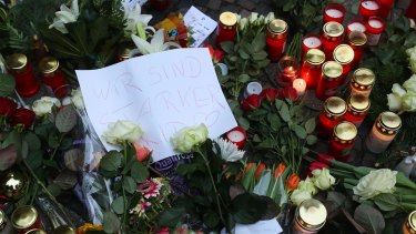 """A message reading """"We are stronger"""" sits among flowers near the scene of the Berlin attack."""