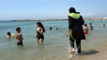 Nissrine Samali, 20, gets into the sea fully clothed in Marseille, southern France. The Cote d'Azur city of Cannes has banned burkinis.