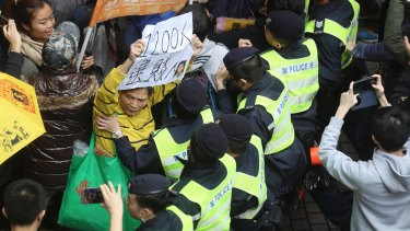 Protesters scuffle with police officers during a protest against the chief executive election in Hong Kong.