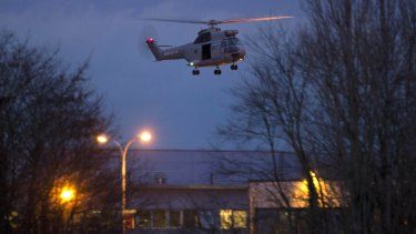 A helicopter flies over the printing plant after police stormed the building.