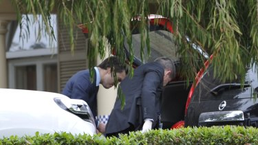 Police examine the boot of a car outside the home of Phil Walsh on Friday.