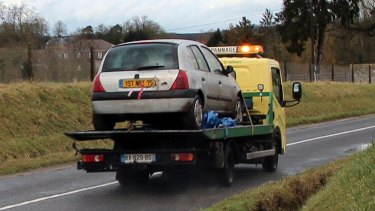 The grey Renault Clio driven by the Kouachi brothers is towed after being found in a forest in north-east of Paris.