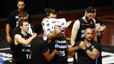 Breakers players applaud Akil Mitchell as he is helped off the court after suffering a serious eye injury.