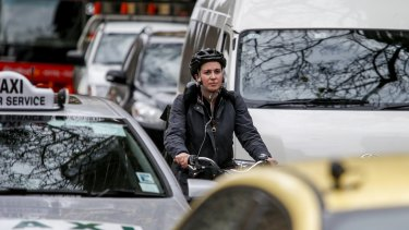 A cyclist in traffic in Melbourne's CBD.