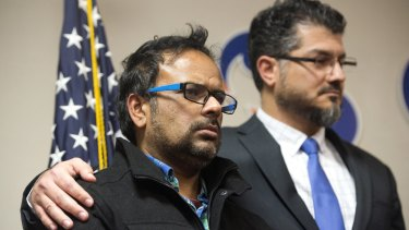Farhan Khan, left, brother-in-law of one of the suspects involved in a shooting in San Bernardino, California, is held by Hussam Ayloush, executive director of the Council on American-Islamic Relations, during a news conference on Wednesday.