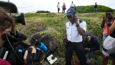 National Police Brigadier Gisele Cadar stands over the plastic object at the site where it was hidden from the media by the man who found it.