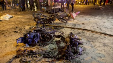 Wreckage of motorcycles are seen as security forces and emergency workers gather at the scene of a blast in central Bangkok on Monday.