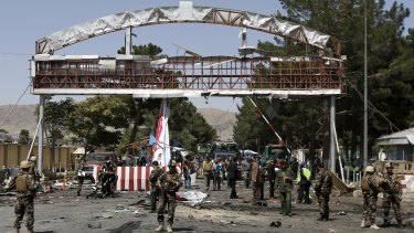Members of the Afghan security forces stand at the site of a car bomb blast at the entrance gate to the Kabul airport on Monday.