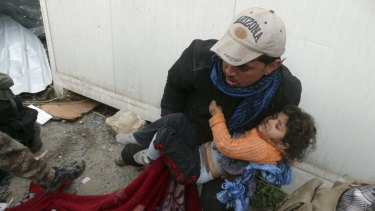 A child is comforted as Iraqi security forces help trapped civilians.