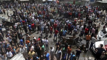 Citizens inspect the scene at the crowded market in Sadr City.