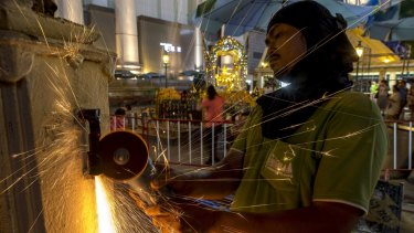 A worker fixes a fence at the Erawan Shrine after Monday's deadly blast.