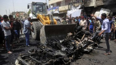A bulldozer cleans up after the car bomb at a crowded outdoor market in the Iraqi capital's eastern district of Sadr City.