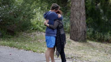 Two people comfort each other outside the Eltham North home.