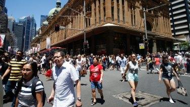 Pedestrians cross George Street in front of the Queen Victoria Building in Sydney.