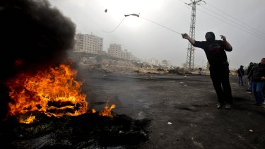 A Palestinian protester uses a slingshot to hurl stones at Israeli troops during clashes in Ramallah on Wednesday.