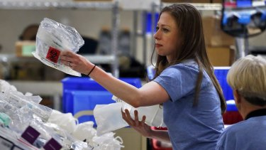 Chelsea Clinton works with volunteers preparing free medical kits for distribution around the world.