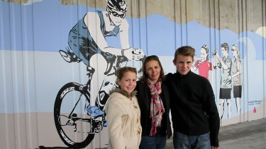 Leslie Karayan, a cyclist who lost his life when a truck hit the Annerley Road rail  bridge in Dutton Park two years ago, has been commemorated at the site with a street mural. His wife Kerri Karayan and two kids Sabine, 10, and Alessandro, 13, stand in front of the mural that depicts their dad and the family as well as other cycling friends, at the unveiling on Saturday.