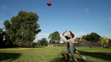 Boys play football on the Reservoir land Melbourne Water wants to rezone and sell.