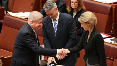 Employment minister Senator Michaelia Cash is congratulated by Communications Minister Mitch Fifield and Finance Minister Senator Mathias Cormann for the passing of the ABCC bill on Wednesday.