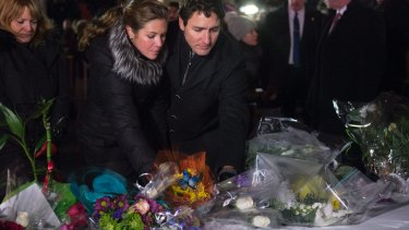 Canadian Prime Minister Justin Trudeau and his wife Sophie Gregoire Trudeau place flowers at a makeshift memorial on Monday.