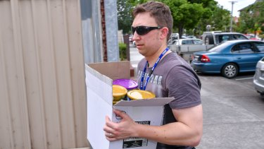 A detective carries a box of the stolen baby formula.