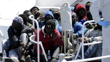Migrants wait before disembarking from a Coast Guard boat.